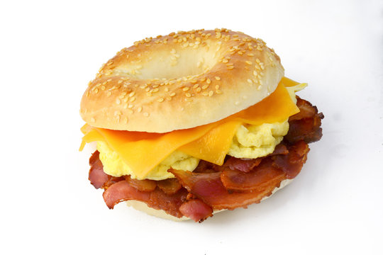Bagel with fried bacon, scrumbled eggs and cheddar cheese. Studio isolated