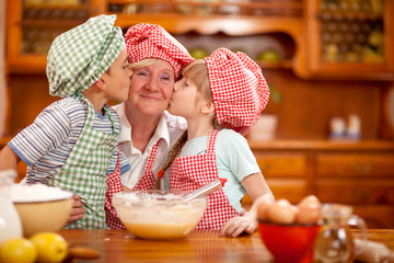 grandson and granddaughter kiss their grandmother in the kitchen