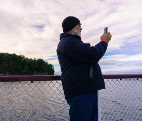 senior man taking pictures with mobile phone, enjoying lake cruise