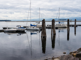 sail boats docked at pier with Adirondack mountains across the lake