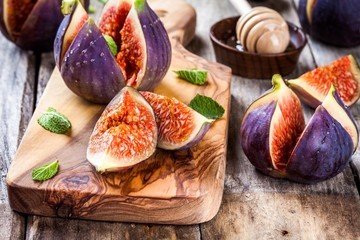 Fresh ripe figs with honey and mint leaves