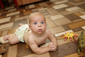 Serious baby boy crawling on the floor