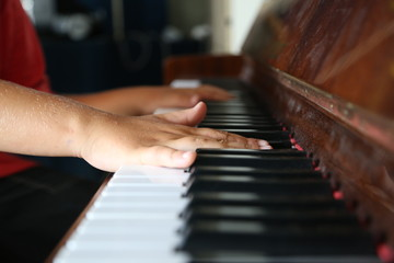 Hands of kid playing on a piano keyboard shot from above