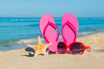 The sea, beach, sand and women's accessories: pink flip-flops, red sunglasses and starfish
