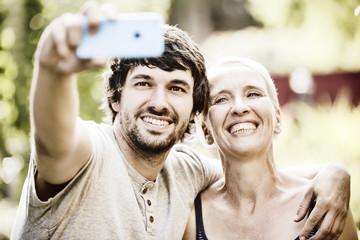 Mutter und erwachsener Sohn machen ein Selfie im Garten