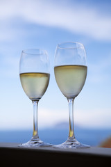 A restaurant table on a beach with glasses of fresh white wine.