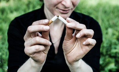 A woman is sitting in a very depressed mood, in the hands of a broken cigarette.