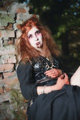 Portrait girl with red hair and bloody face vampire, murderer, psycho, halloween theme, bloody woman