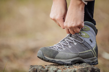 woman on a hiking trail ties the shoelace on her walking shoe,