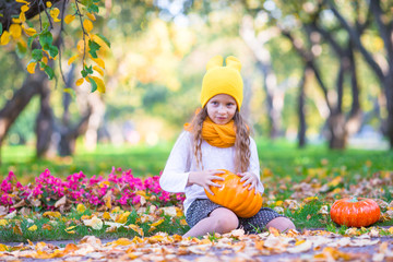 Wall Mural - Adorable little girl with pumpkin outdoors at beautiful autumn