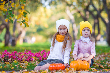 Wall Mural - Happy little girls with pumpkins ready for Halloween outdoors at