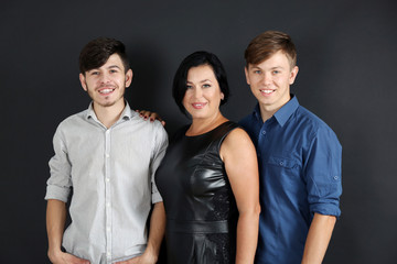 Portrait of mother and her sons on dark background
