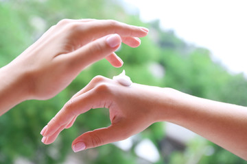 Women applying cream on her hands outdoor