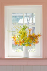 Artificial flowers in white vase beside white window.