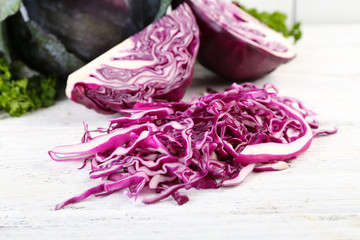 Cut red cabbage and parsley on wooden table