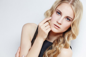 Portrait of young blond woman over grey background.