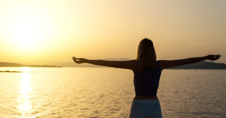 Woman with arms wide open at sunset.