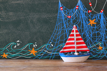 photo of wooden sailing boat in front of chaklboard with nautical illustrations.