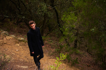 stylish young handsome man in forest