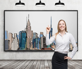 A beautiful lady is pointing out the picture of New York City on the wall. Wooden floor, concrete wall and three black ceiling lights.