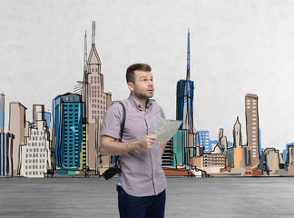 A handsome tourist in casual clothes is trying to find the best tourist place. New York sketch on the background. A concept of modern tourism.