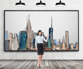 A brunette lady is pointing out the picture of New York City on the wall. Wooden floor, concrete wall and three black ceiling lights.
