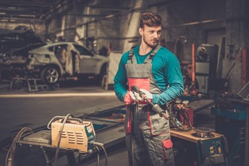 Mechanic with welding machine in a workshop