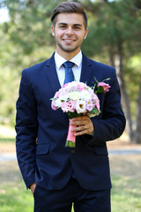 Groom holding wedding bouquet outdoors