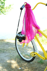 Old bicycle with camera and pink scarf, outdoors
