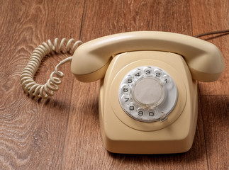 Retro telephone on wooden table in front gradient background