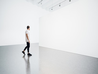 Young man walking in the empty, white gallery