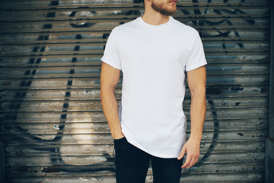 Young man wearing white blank t-shirt and blue jeans, standing