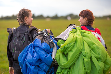 Two professional women parachutists are open parachutes behind