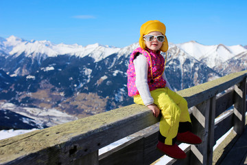 Happy child enjoying winter holidays in Alpine resort in Austria. Active sportive toddler learning to ski. Kids having fun outdoors. Beautiful Alps mountains in the background.