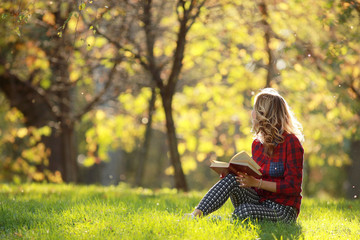 girl in a sunny park reading a book