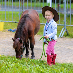 Lovely cowgirl feeding with grass little pony horse in the farm. Pretty preschooler girl wearing...