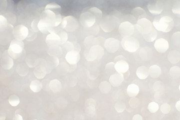 Silver white glittering Christmas lights. Blurred abstract backg