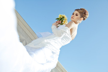 Beautiful bride with bouquet on the beach restaurant
