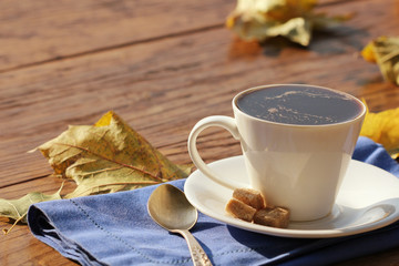 Coffee cup on a wooden background in fall time