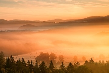 Pink daybreak in hilly landcape. Autumn freeze misty morning in a beautiful hills. Peaks of hills are sticking out from pink orange fog