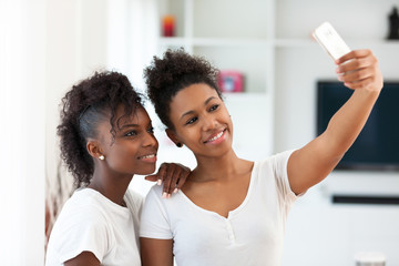 African American teenage girls taking a selfie picture with a sm