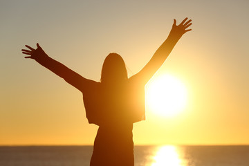 Free woman raising arms watching sun at sunrise