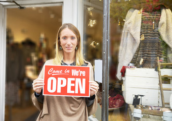 Saleswoman in front of store showing open sign