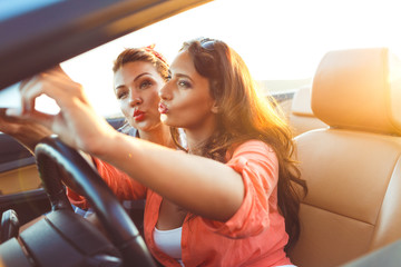 Two young beautiful girls are doing selfie in a convertible