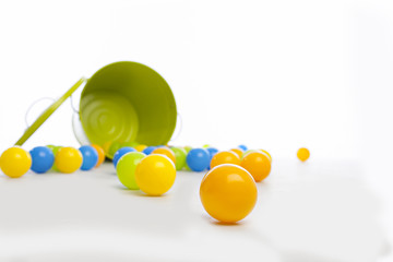 close up of yellow ball wiht green metal bucket that has spilled a large number of multi-colored balls on a white backdrop and floor