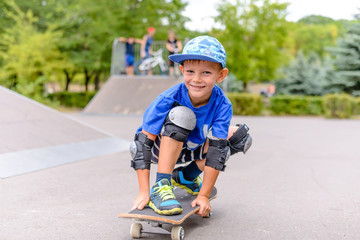 Small boy on his skateboard grinning at the camera
