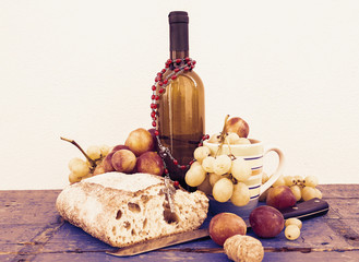bread grapes and a bottle of wine over wooden boards