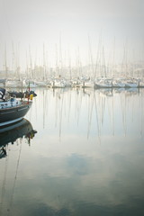 Boats moored during a dense fog in the marina at Lagos, Algarve,