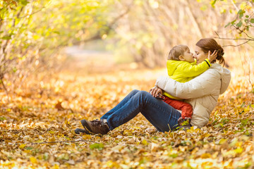 Happy woman and her little son having fun in an autumn park. The boy kissing mother in nose.