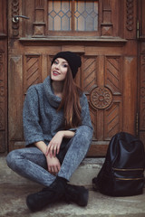 Happy young smiling hipster woman sitting near the door. Street fashion concept. Toned